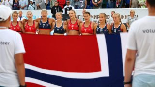 Members of Norway's Women's Beach Handball team stand in a line behind their flag.