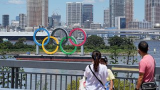 A family stands in front of the oversized Olympic rings. The rings stand on a raft in Tokyo Bay in front of the Odaiba district. The 2020 Tokyo Olympics will take place from 23.07.2021 to 08.08.2021.