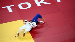 France's Amandine Buchard (white) competes with Switzerland's Fabienne Kocher during their judo women's -52kg semifinal A bout during the Tokyo 2020 Olympic Games at the Nippon Budokan in Tokyo on July 25, 2021.