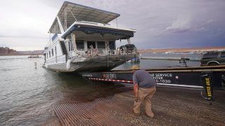 A family's houseboat is pulled from the Wahweap launch ramp after a three-week vacation at Lake Powell