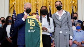 President Joe Biden, left, poses for a photo with Seattle Storm's Jewell Loyd, center, and Breanna Stewart, right, during an event in the East Room of the White House in Washington, Monday, Aug. 23, 2021, to celebrate their 2020 WNBA Championship.