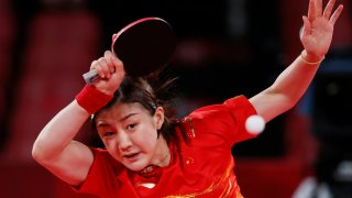 Red-clad Chen Meng of China watches her shot in a semifinal versus Germany