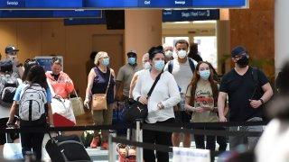 Passengers wearing face masks arrive at Orlando International Airport.