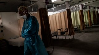 Registered traveling nurse Patricia Carrete, of El Paso, Texas, walks down the hallways during a night shift at a field hospital set up to handle a surge of COVID-19 patients, Wednesday, Feb. 10, 2021, in Cranston, R.I. Rhode Island's infection rate has come down since it was the highest in the world two months ago and many of the field hospital's 335 beds are now empty. On quiet days, the medical staff wishes they could do more.