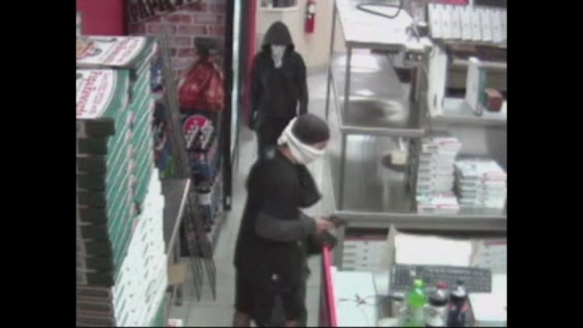 According to the surveillance video, the two men, one of which was armed with a gun, walked into the Papa John's at 50 Indian Trace and held the general manager at gunpoint, demanding he place money inside one of the pizza delivery bags, Weston Police said.