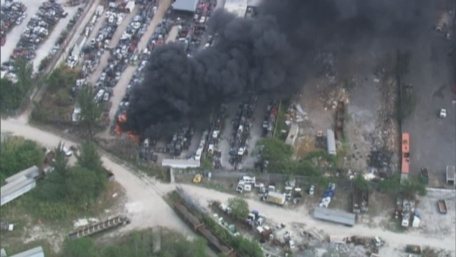 Firefighters battle a blaze at a junkyard in Opa-locka.
